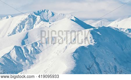 Snow-covered Mountains. Peaks Touching The Sky. Beautiful Cloudy Blue Sky In The Background. Snowy W