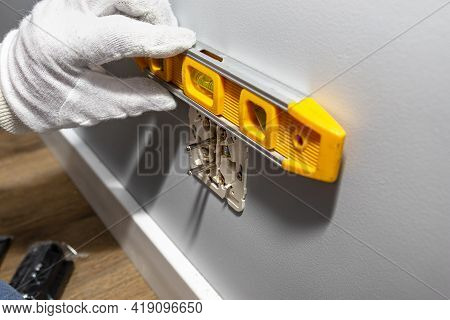 An Electrician Inserts A Double Grounded Electrical Outlet Into The Electrical Box In The Wall Of Th