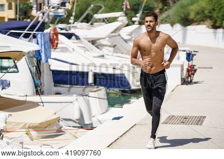 Young Man With An Athletic Body Running Shirtless Through A Harbour.