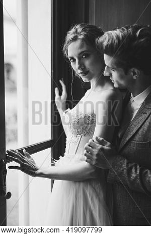 Groom Hugs Bride From Behind At The Large Window Of An Old Villa. The Bride Looks At The Camera And