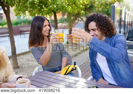 Couple Of Friends Toasting While Having A Drink With Their Multi-ethnic Group Of Friends