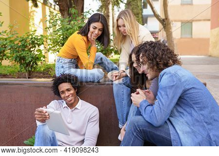 Multi-ethnic Group Of Young People Looking At A Digital Tablet Outdoors In Urban Background.