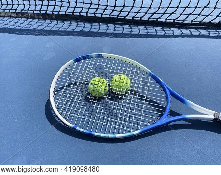 One Tennis Racket Lying On Top Of Two Yellow Tennis Balls On A Blue Court Close To The Tennis Net.