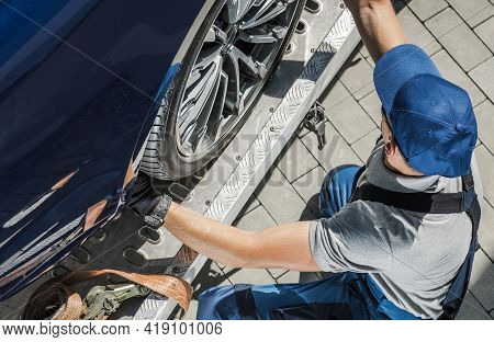 Caucasian Automobile Towing Worker In His 40s Securing Car On His Tow Truck. Transportation And Auto