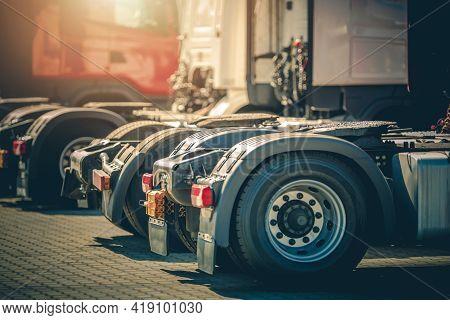 Modern Brand New Semi Truck Tractors In Line On Dealership Parking Lot. Heavy Duty Transportation An