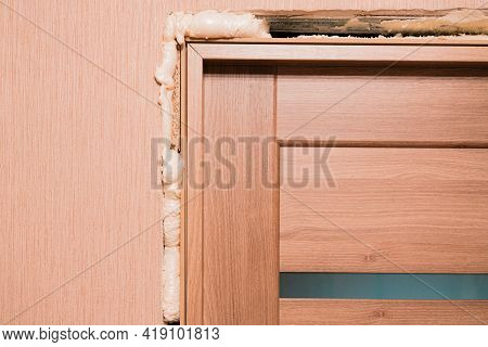 Filing Foam Around The Just Installed Wooden Door With Glass Inserts In The Room. Repair. Polyuretha