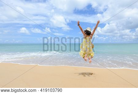 Excited Energetic Happy Tourist Girl Is Jumping At The Beach On Summer Vacations, Fun And Freedom Wi