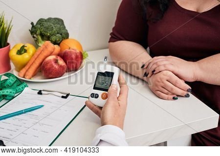 Measuring Blood Sugar. Nutritionist Using Glucometer Tests Overweight Womans Blood Sugar, Prevention