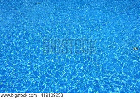 Rippled Blue Water Surface. Water Level In The Pool. Light Reflections On The Surface Of The Water F