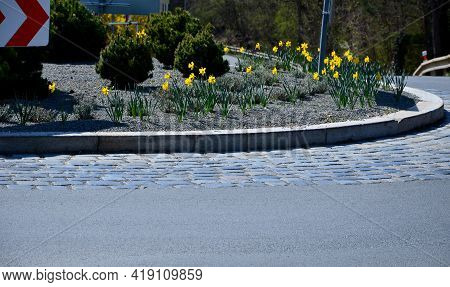 Roundabout Of Paving Gray Granite Cubes, Transport Hub, With Flowers And Grasses In The Middle Of Th