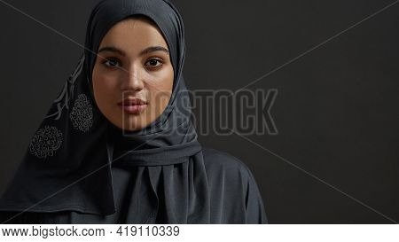 Portrait Of Young Arabian Girl Wearing Traditional Hijab And Looking At Camera While Posing On Dark