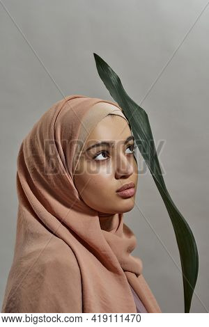 Portrait Of Young Arabian Woman In Hijab With Green Leaf While Looking Up On Light Background, Verti