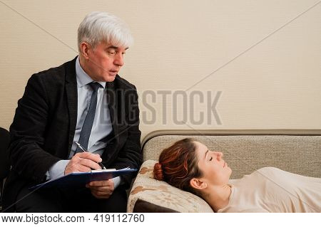 Caucasian Woman Lies On A Couch At A Reception With A Psychotherapist. An Elderly Man Works As A Psy