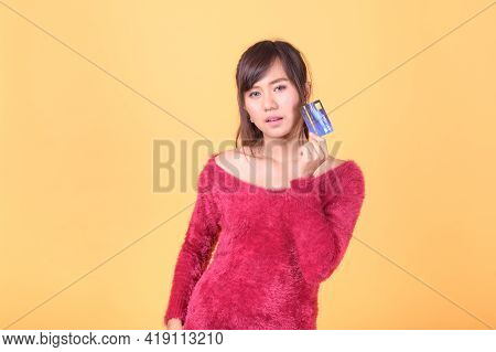 A Beautiful Asian Woman Is Happy And Thinks That She Will Spend With Many Of Her Credit Cards