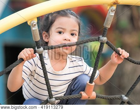 Young Asian Girls Are Having Fun Clambering On Rope Nets In A Playground