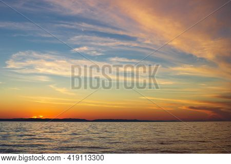 Light Clouds On Blue Sky In Yellow Pink Tones, Sunset On Lake, Beautiful Scenic Seascape Of Calm Sea