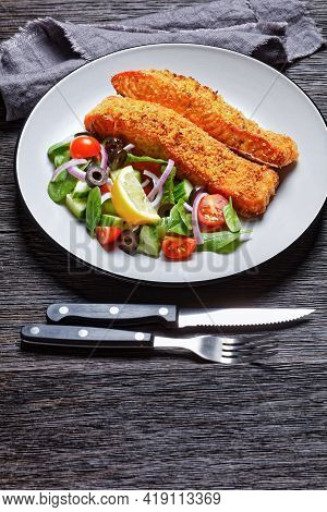 Panko Crusted Baked Salmon Fillets With Spinach Tomato Cucumber Olives Salad On A Plate On A Dark Wo