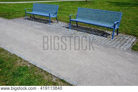 Park Benches In Light Blue Made Of Metal Strips Similar To A Lattice. Trash Can And Beautiful Lawn W