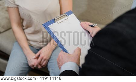An Elderly Male Psychotherapist Talking To A Female Patient And Taking Notes On A Clipboard. Close-u