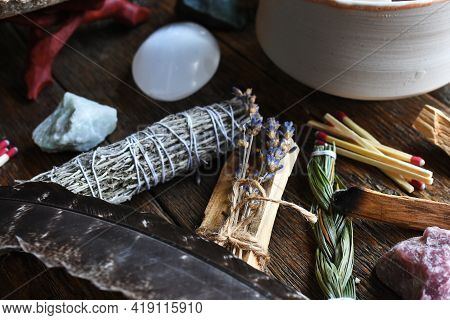 A Close Up Image Of Several Different Types Of Healing Incense And Healing Crystals On A Dark Wooden