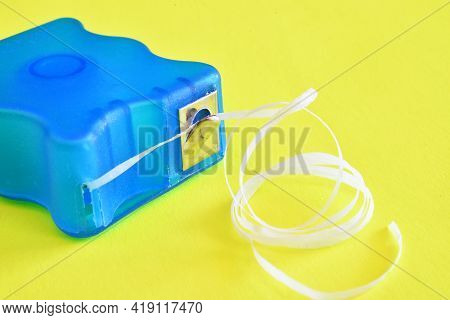 A Close Up View Of A Bright Blue Dental Floss Container On A Yellow Background.