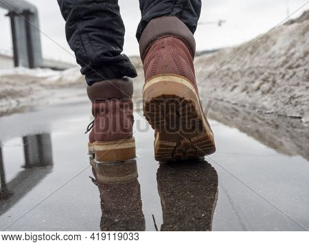 A Woman Walks Through A Puddle In Terracotta Leather Shoes. Close-up, Reflection In A Puddle, Litter