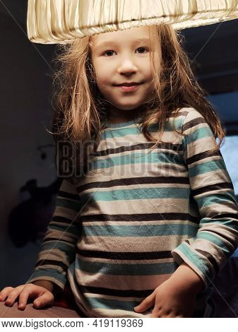 Kid In Shade, Happy Pretty Little Girl Plays With Lampshade Like Hat. Funny Portrait Of Adorable Chi