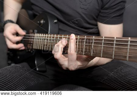 A Man Playing Black Electric Guitar. Guitar Fretboard Close-up. Learning To Play The Guitar. Hand Gr