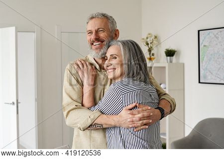 Happy Senior Adult Mature Classy Couple Hugging, Bonding, Thinking Of Good Future. Carefree Cheerful
