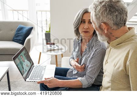 Mature Old Grandparents Couple Patients Having Video Chat With Virtual Doctor Using Laptop Computer