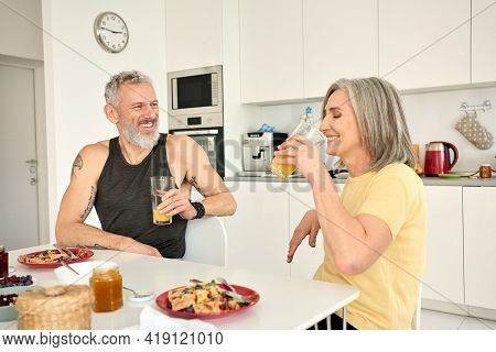 Happy Healthy Fit Mature Old Couple Having Breakfast Sitting At Kitchen Table. Smiling Senior Mid Ag