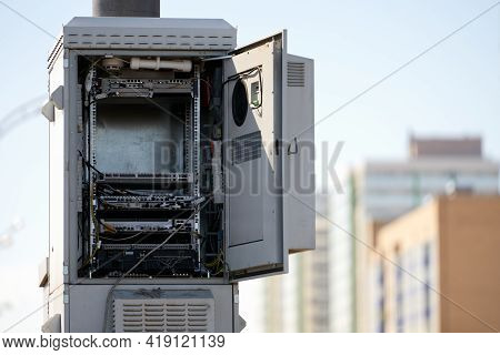 The Case Of The Cellular Base Station Unit With An Open Door On The Background Of High-rise Building