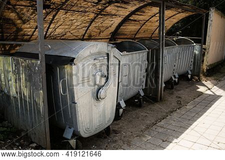 Empty Large Gray Garbage Containers In A Row On A Sunny City Street. Row Of Gray Metal Trash Cans On