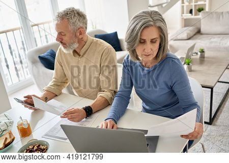 Serious Mature Senior Old Couple Reading Documents Bills Paying Bank Loan Online Together Using Lapt
