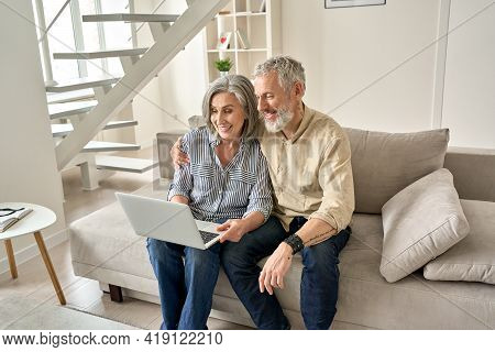 Happy Old Mid Age Family Couple Using Laptop Computer Sitting On Couch. Smiling Senior Mature Husban
