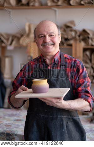 Senior Happy Hispanic Craftsman Standing In Studio.