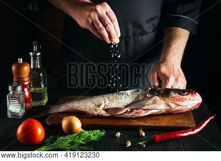 Cook Or Chef Prepares Fresh Fish Bighead Carp Sprinkling Salt With The Ingredients. Preparing To Coo