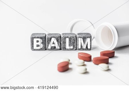 Word Balm Is Made Of Stone Cubes On A White Background With Pills. Medical Concept Of Treatment, Pre