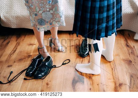 Scottish Wedding Preparations. Man In A Kilt Stands Next To Woman In A Skirt With High-heeled Shoes.