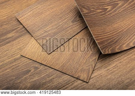 Pvc Vinyl Sample. Vinyl Floors. The Swatches Are Brown With A Woody Texture. Copy Space