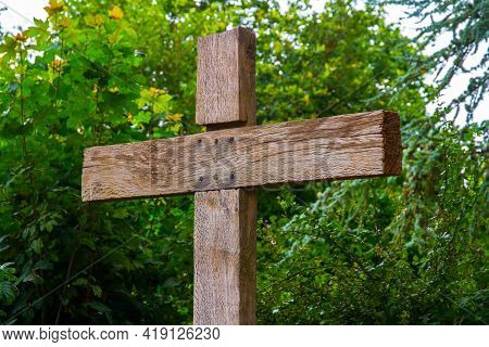 Top Of Wood Wooden Cross Crucifix With Green Foliage Background Outside.