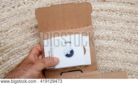 Paris, France - May 2, 2021: Unboxing Process Of New Airtag - Small Device Helps People Keep Track O