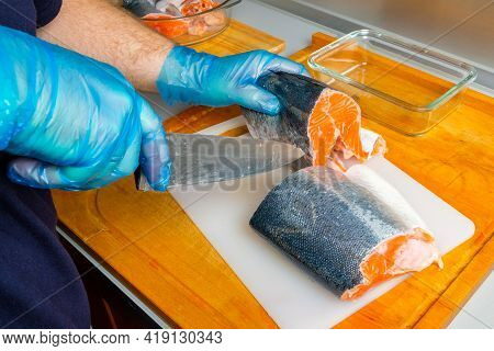 The Hands Of The Cook In Hygienic Gloves Cut The Body Of A Salmon With A Knife. Cutting Fresh Fish I