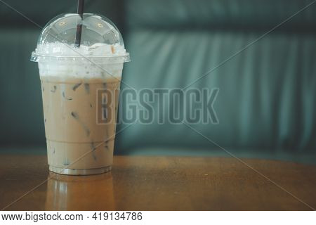 Iced Coffee Mocha In Plastic Glass On The Wood Table In Cafe With Gray Sofa Background