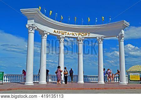 Alushta, Crimea, Ukraine - Jun 01, 2013: Tourists Walking Near Big Colonnade With Alushta - Resort A