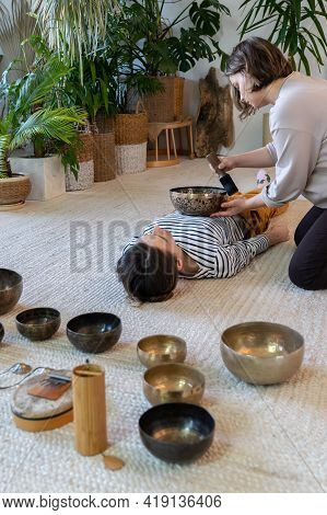 Caucasian Female Getting Sound Massage Therapy With Singing Bowl. Traditional Tibetan Medicine Conce