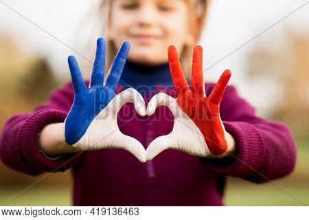 Love And Happiness Concept. Cute Child Forming Heart Gesture With Hands Outdoors On Nature Sunset Bo