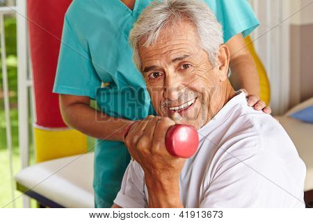 Happy senior man doing dumbbell training at physiotherapy