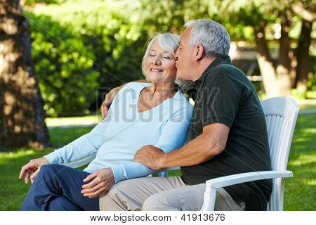 Senior man kissing his woman in a summer garden