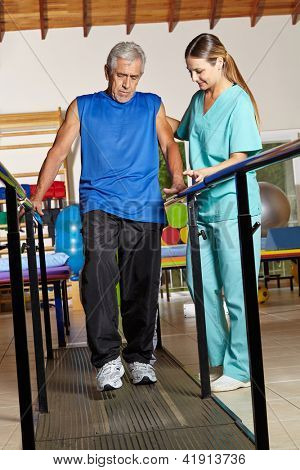 Old senior man at physiotherapy holding on to handles